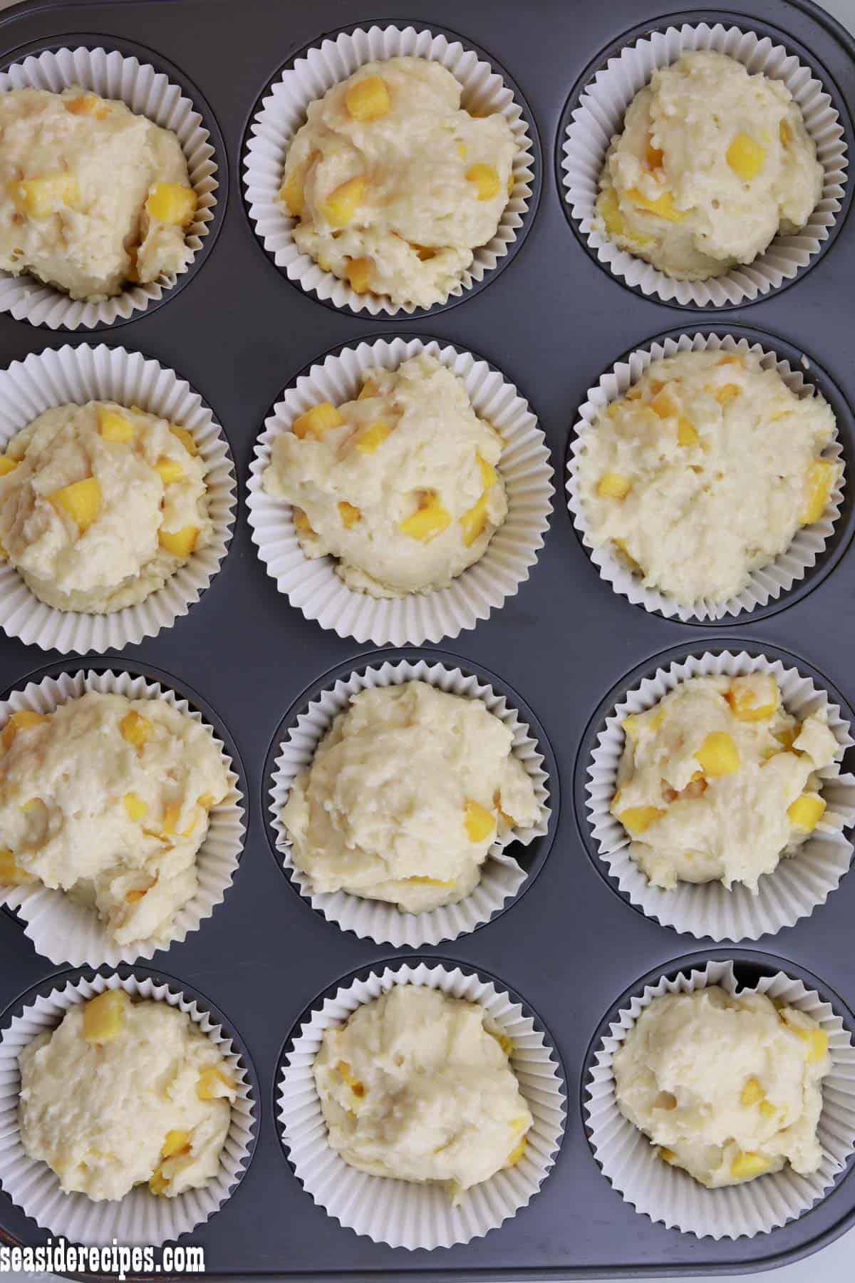 mango muffins batter on muffin tray