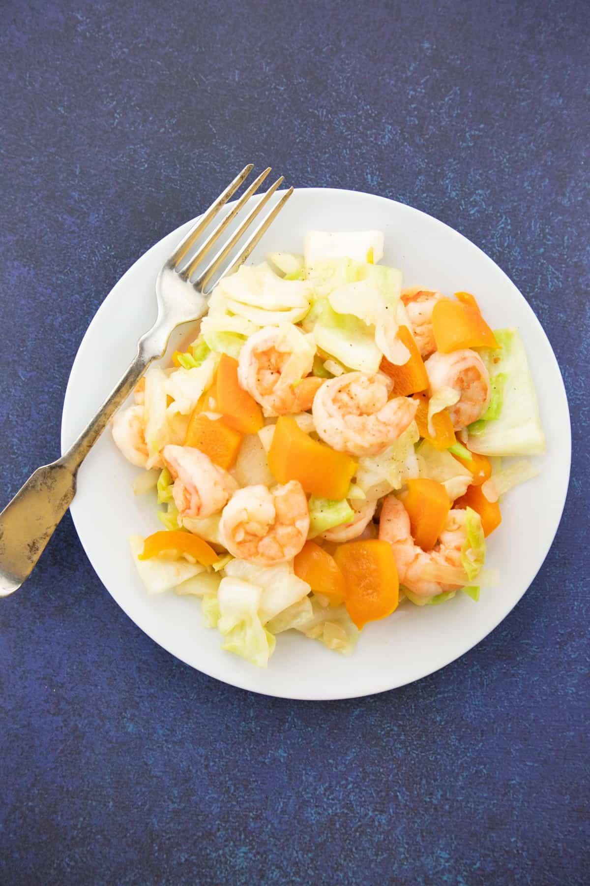 sauteed cabbage with shrimp on white plate with fork with blue background.