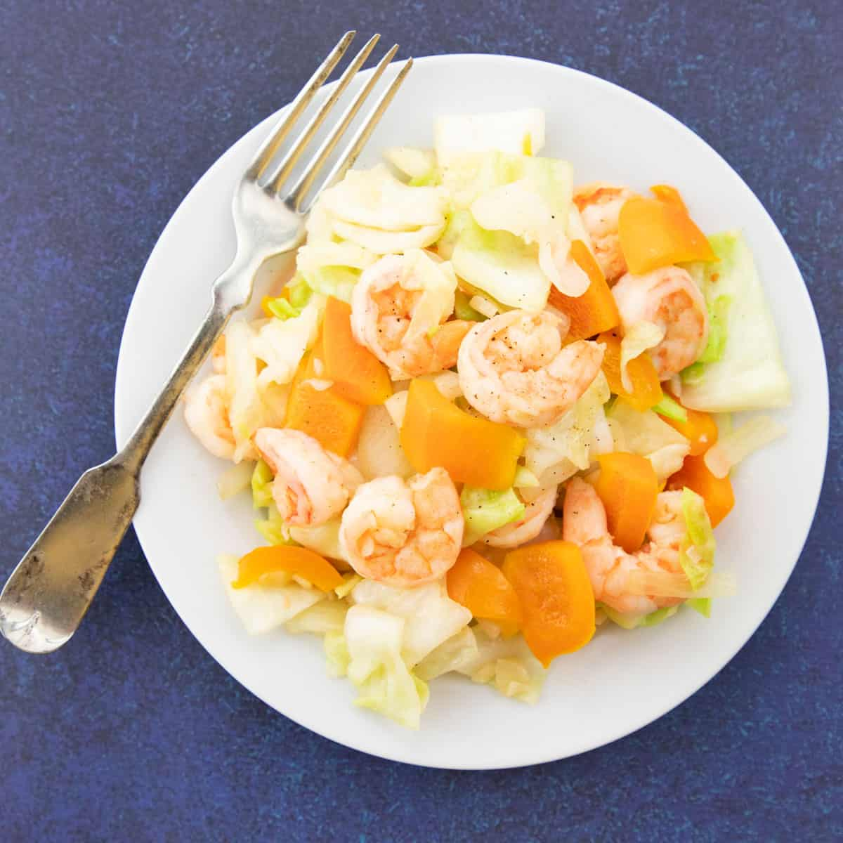 sauteed cabbage with shrimp on white plate with fork.