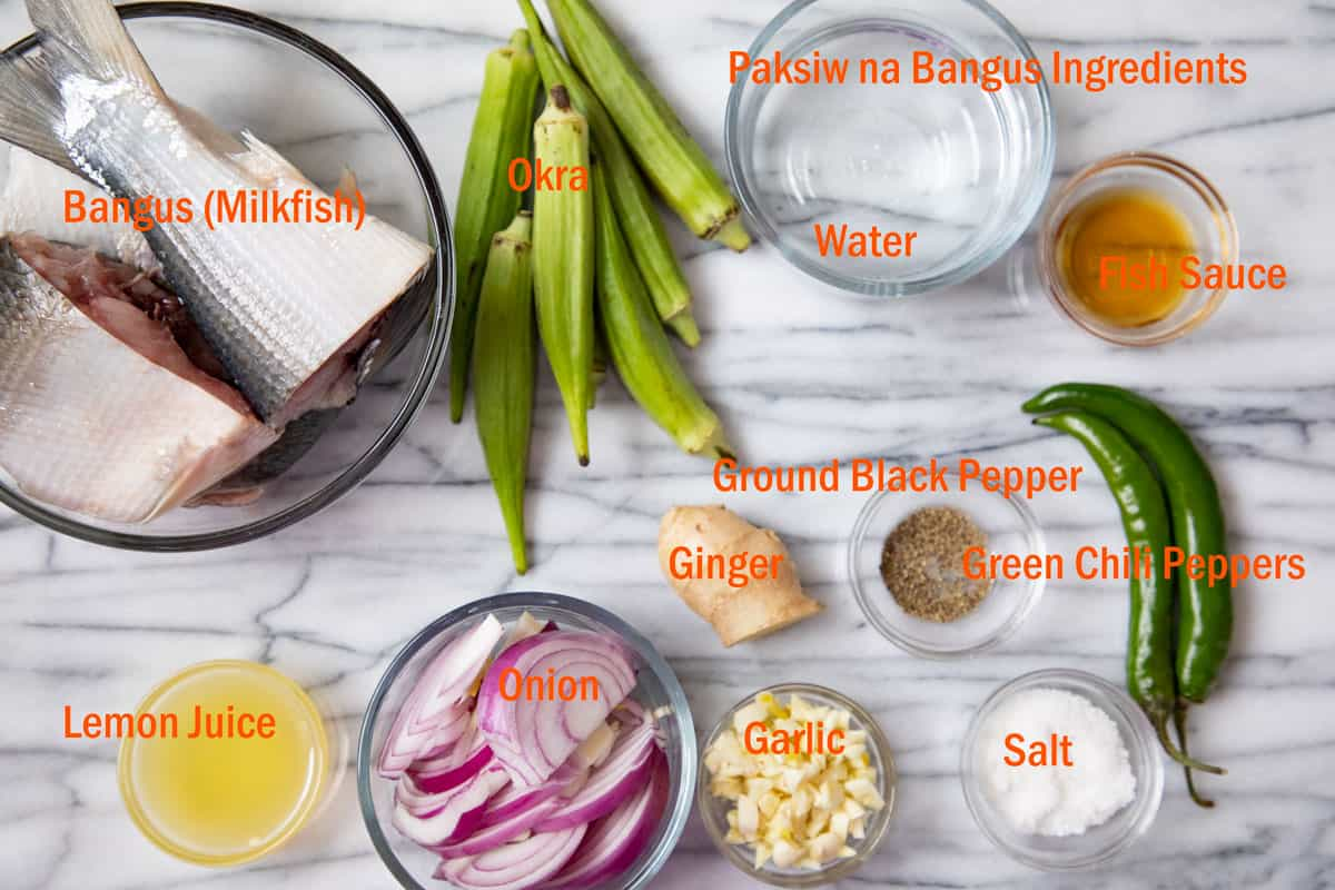 ingredients for fish stew with text overlay on marble countertop.