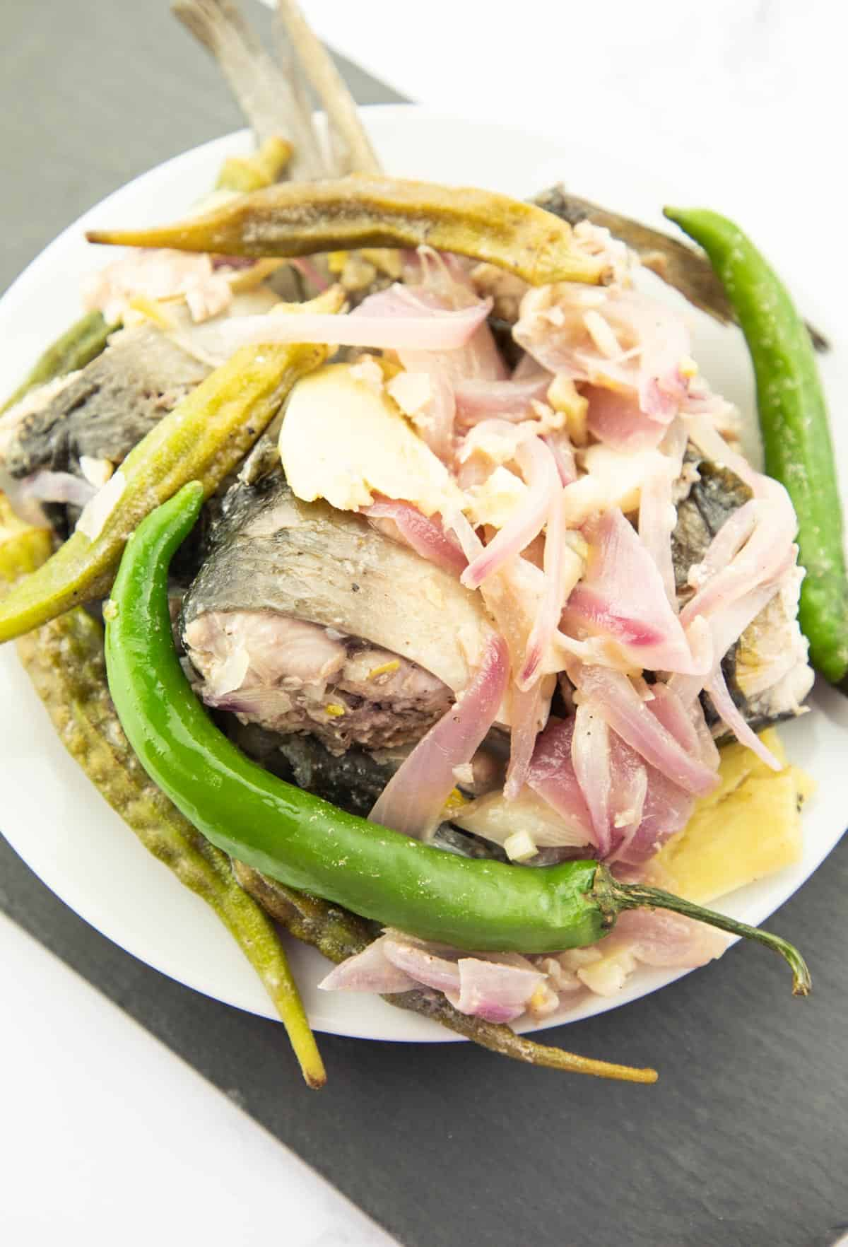 milkfish stewed in lemon juice with okra and green chili peppers on white plate.